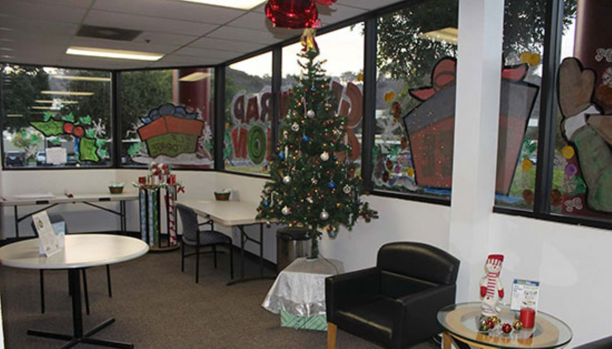 Rolls of gift wrap, Christmas tree, and other holiday decor for the seasonal gift wrapping station in the rental office