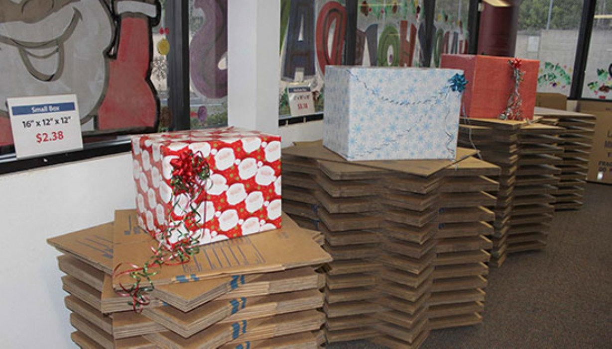 Box displays wrapped in Christmas wrap for holiday gift wrapping station inside the office