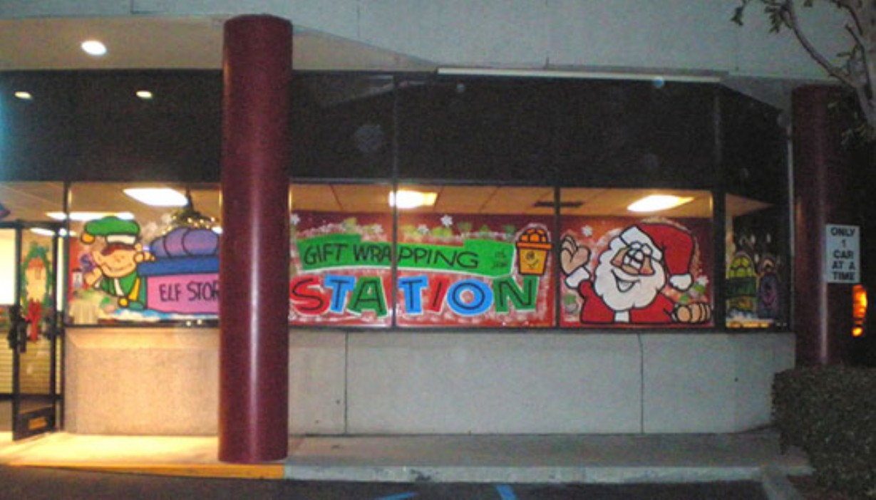Windows and doors painted with elf and Santa Claus holiday theme for gift wrapping station