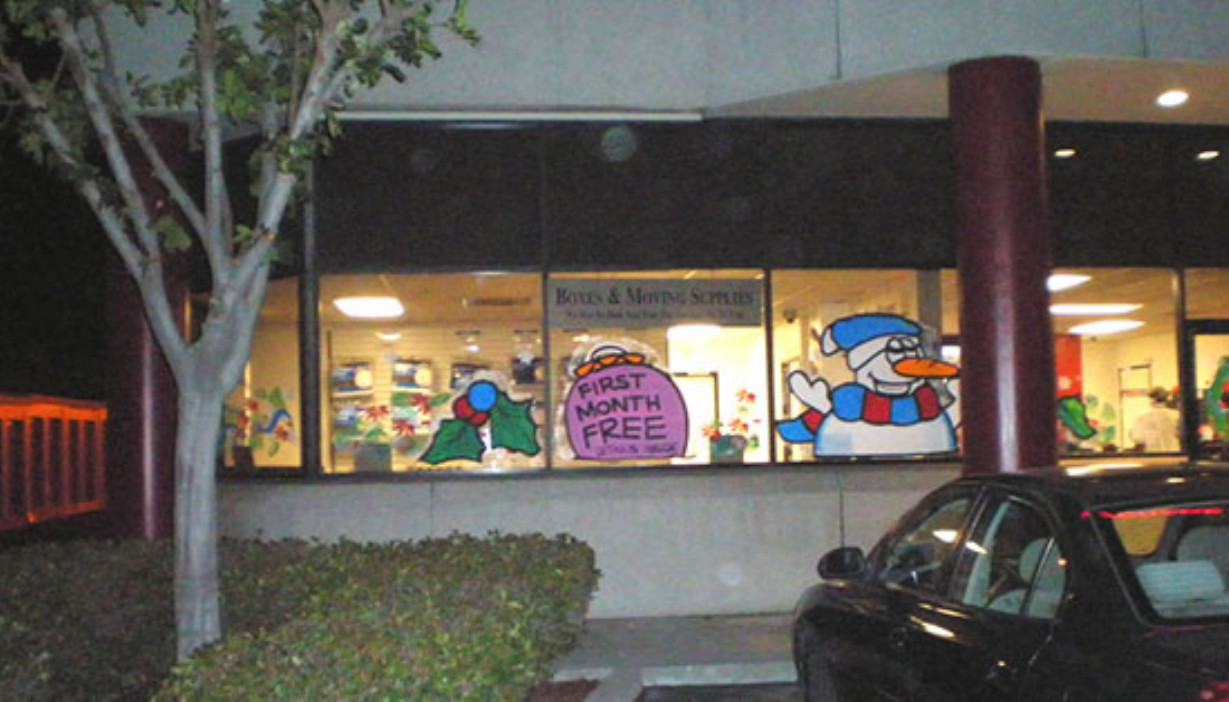 Rental office windows painted with holiday theme and first month's rent free promotion
