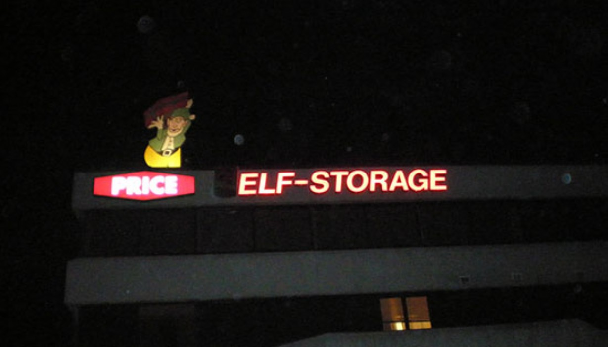 Main building sign lit up at night with elf character on the roof