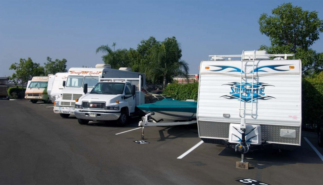 Cars, trucks, boats, RVs and trailers parked in outdoor storage spaces