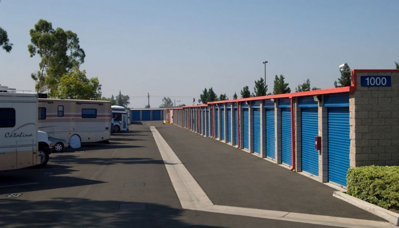 Drive aisle with vehicles and RVs parked left and storage units right