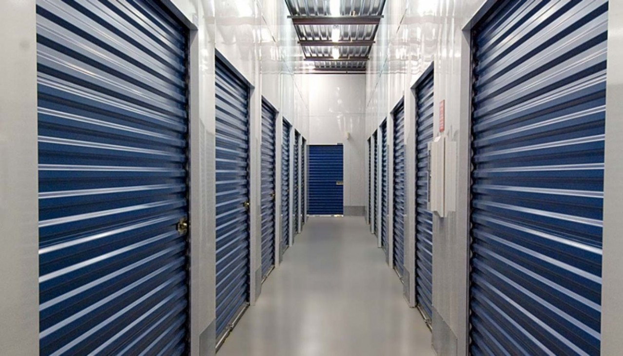 Interior hallway with storage units left and right with blue rollup doors