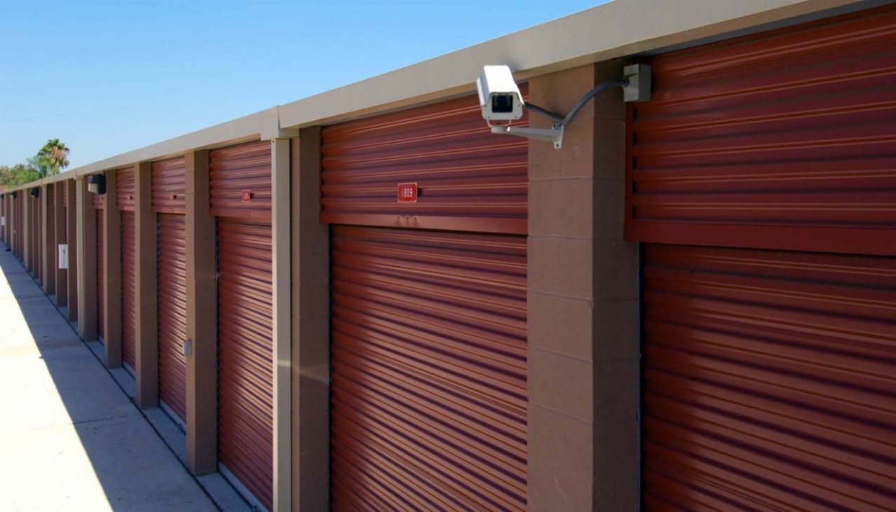 Very large drive up storage units with roll up doors and security camera on the building