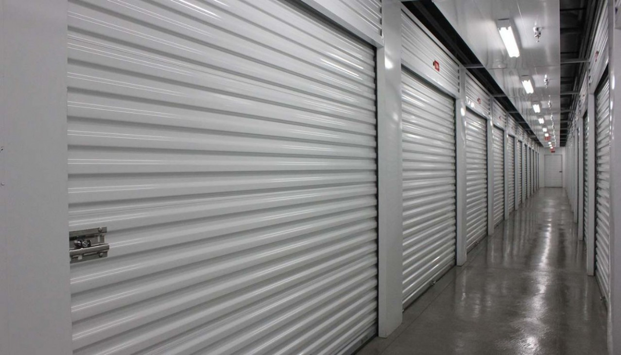 Interior hallway with large storage units with roll up doors left and right