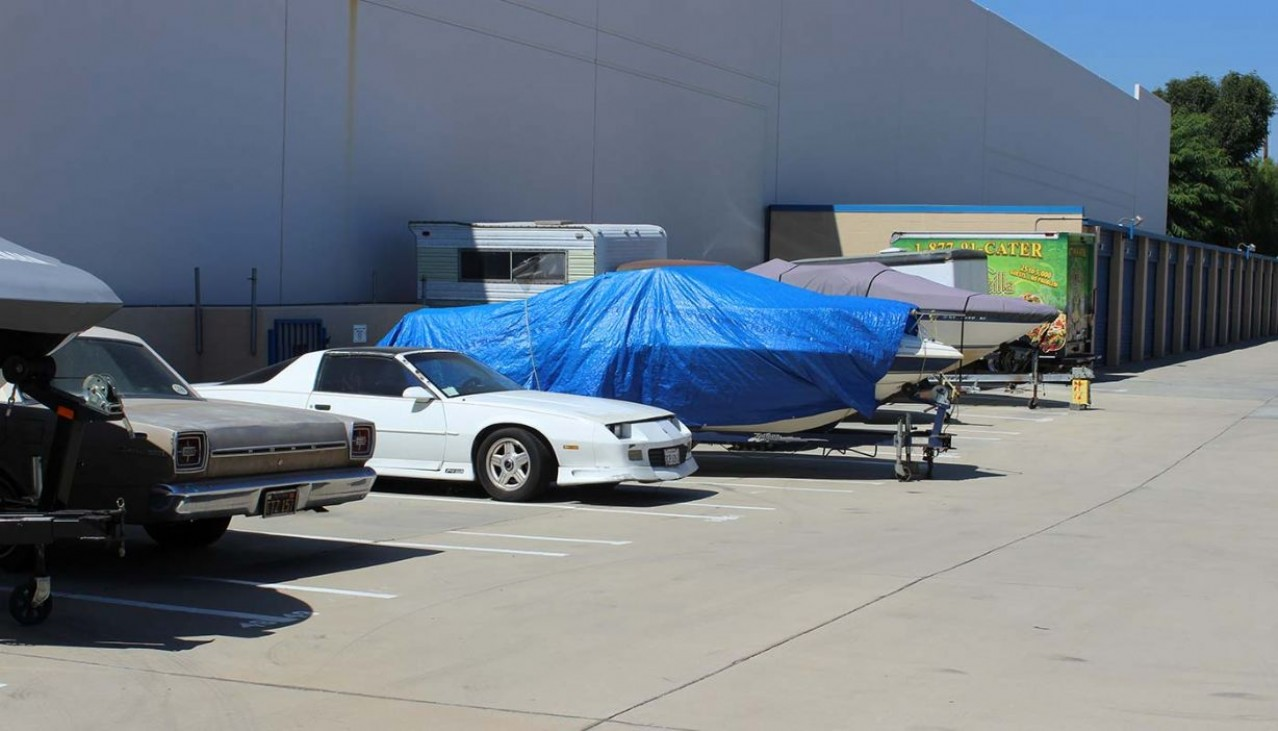 Boat, cars and trailer parked in the outdoor vehicle storage