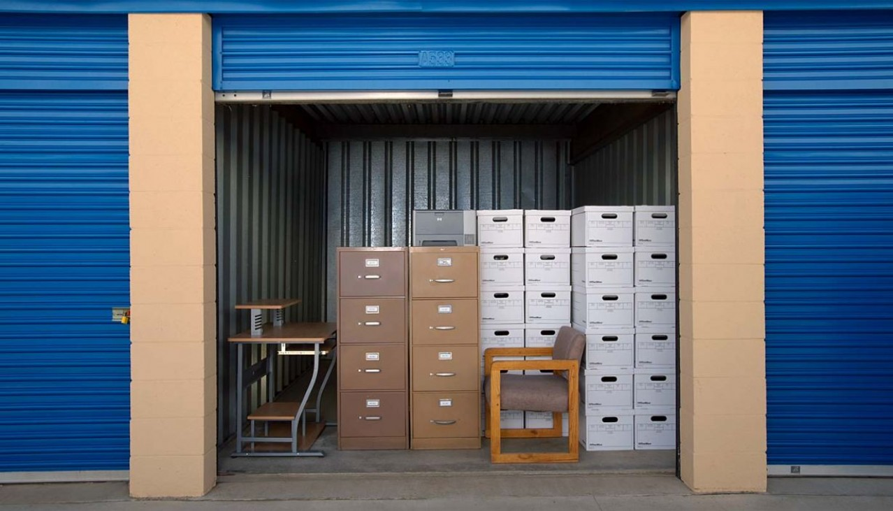 Drive up storage unit with office chairs and boxes stacked inside with door rolled up