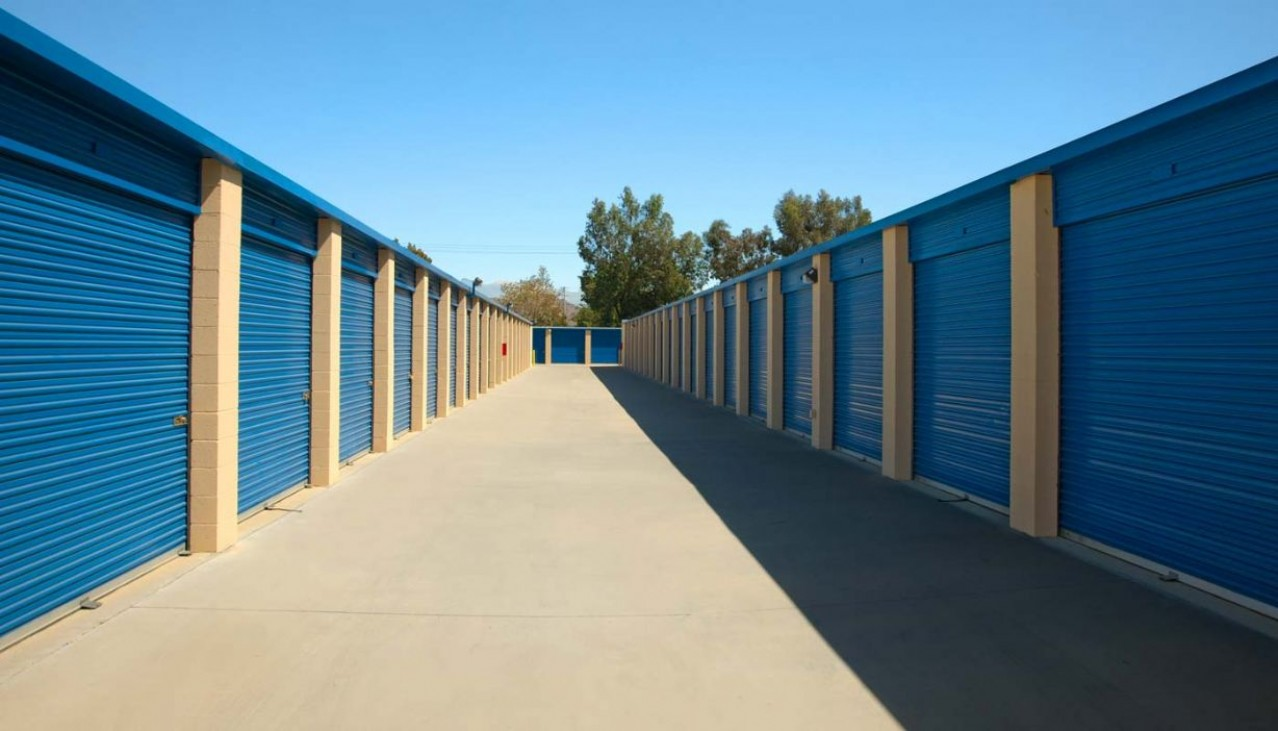 Wide drive aisle of drive up storage units with metal roll up