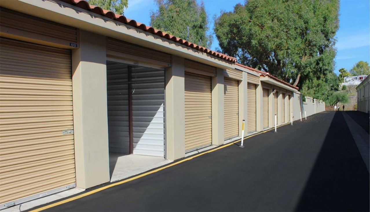 Large drive up storage unit with concrete block and metal interior walls and roll up doors