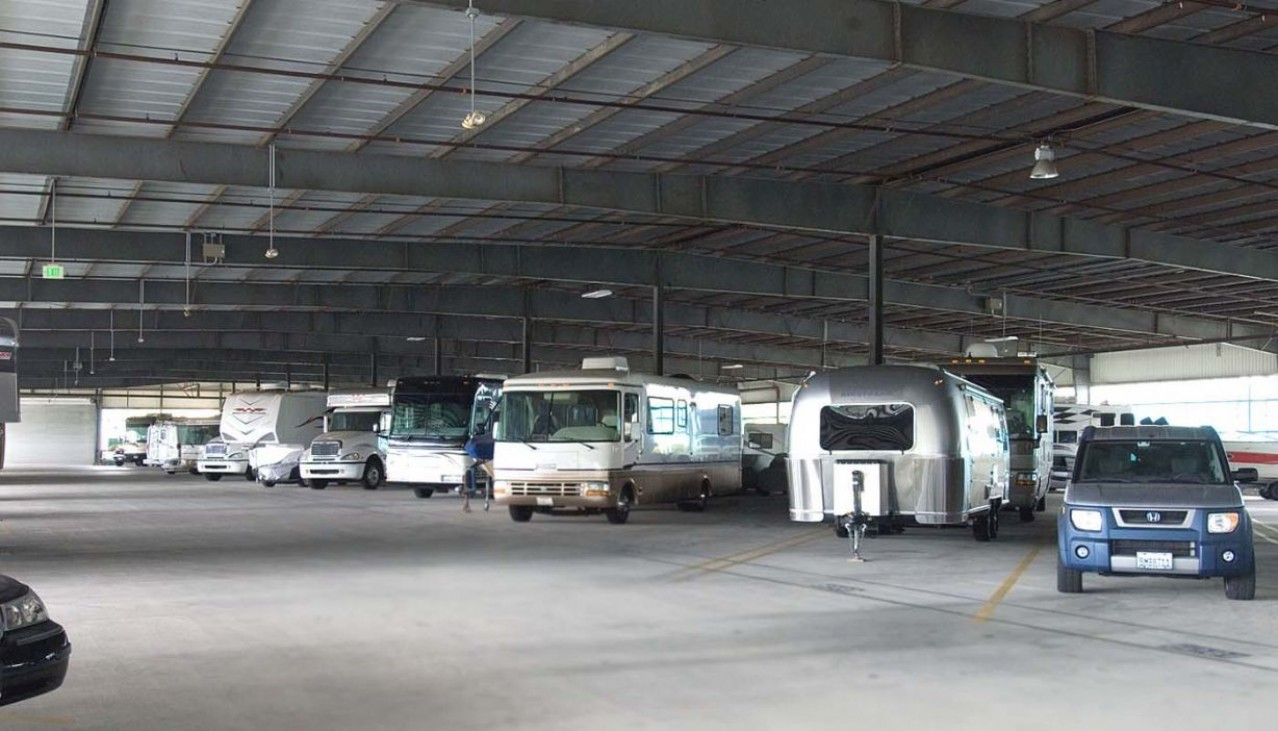 Motorhomes, cars, boats, and trailers parked in the indoor vehicle storage facility
