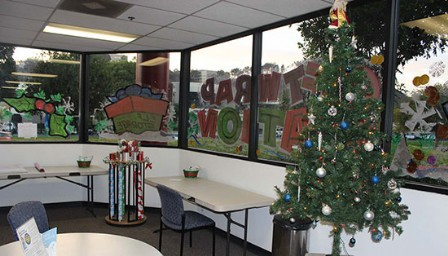 Rolls of gift wrap, Christmas tree, and other holiday decor for the seasonal gift wrapping station in the office