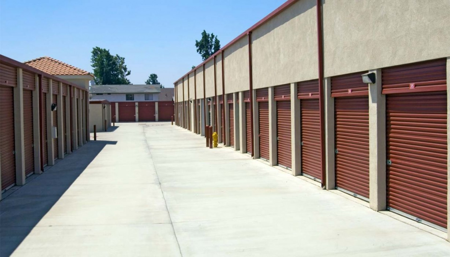 Wide drive aisle to large drive up storage units with roll up doors left, right and center
