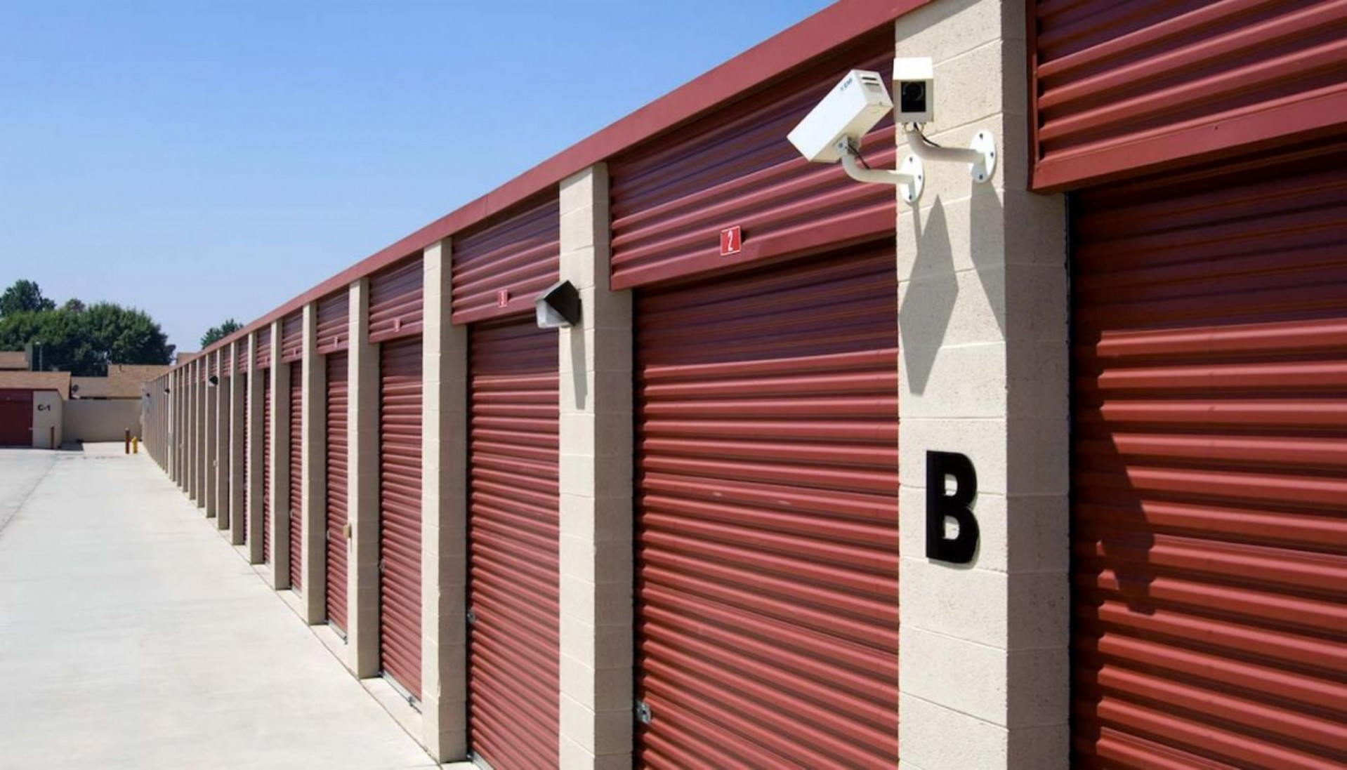 Extra large drive up storage units with roll up doors and security camera on the building