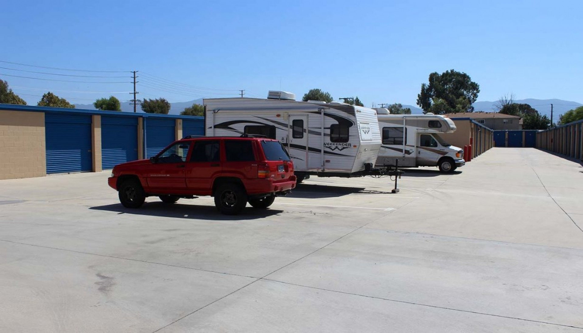 An SUV, travel trailer and small RV parked in vehicle storage spaces
