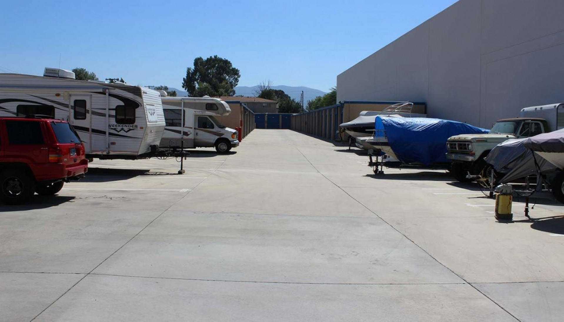 Travel trailer, SUV, small RV, boats and a truck parked in vehicle storage spaces