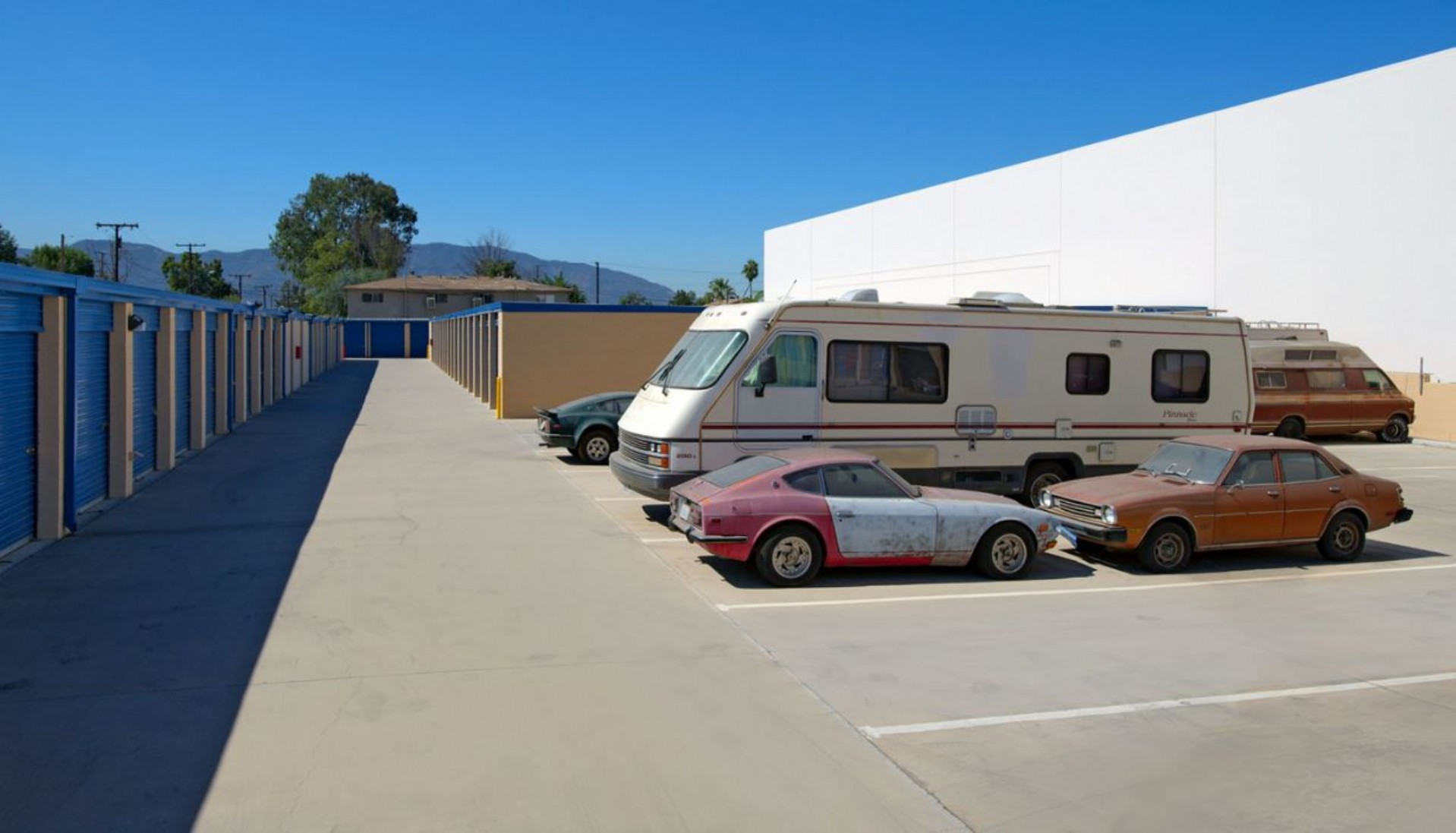 Cars and a large RV parked in vehicle storage spaces