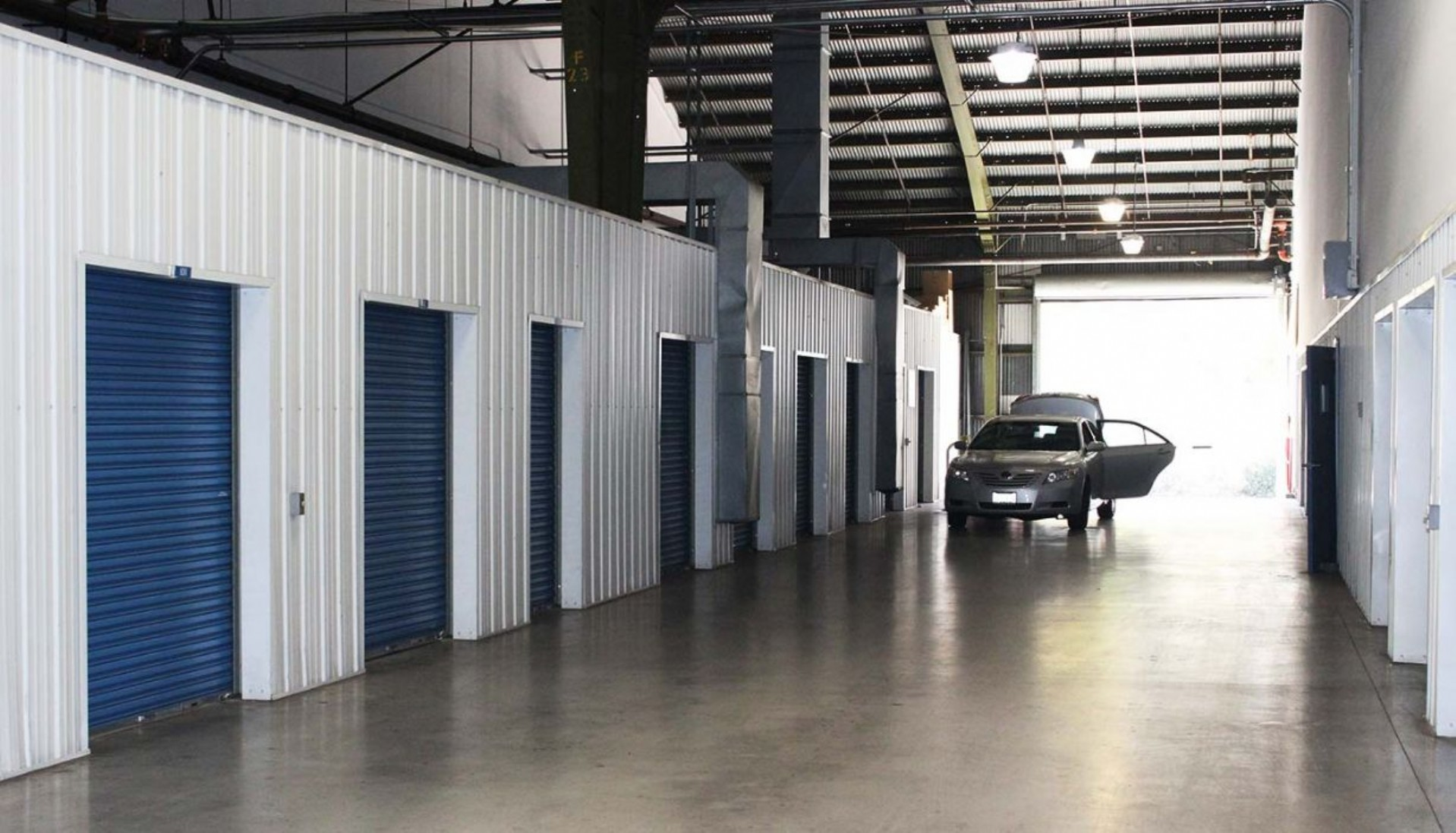 Indoor storage facility with car pulled in next to storage unit