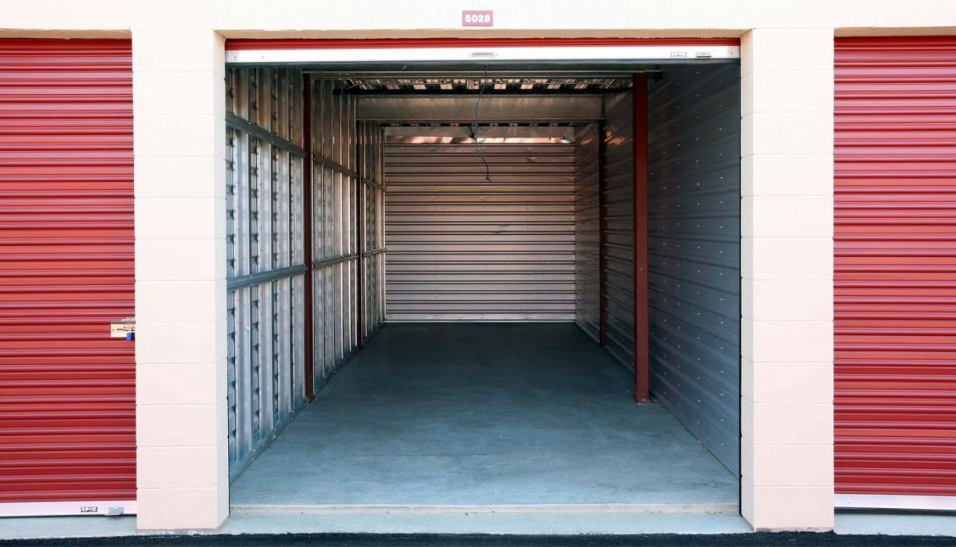 Large drive up storage unit with door rolled up and aluminum interior walls