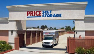 Moving truck driving through the exit gate beneath the Price Self Storage monument sign